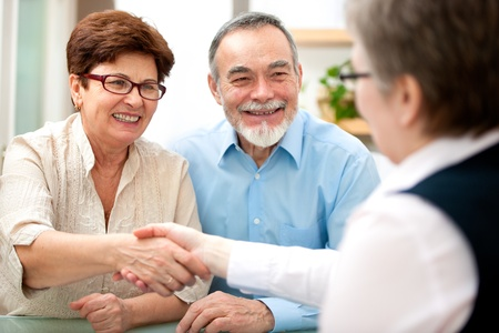organizer: senior couple smiling while shaking hand with financial advisor Stock Photo