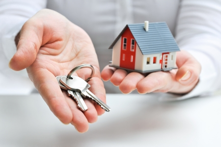house property: Real estate agent with house model and keys Stock Photo