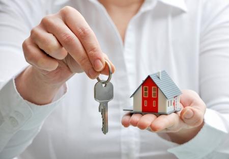 vendedor: Agente de bienes ra�ces con el modelo y claves de la casa Foto de archivo