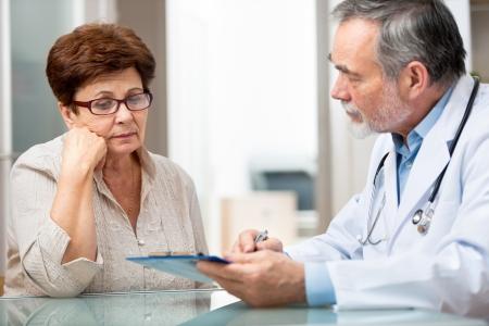 enfermera con paciente: m�dico hablando con su paciente en el consultorio Foto de archivo