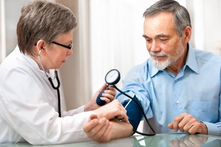 medico misura la pressione sanguigna del paziente maschio