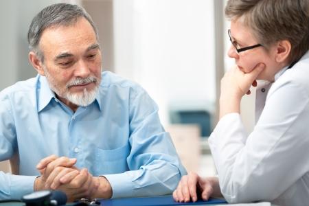 paciente: Doctora hablando con su paciente de sexo masculino en la oficina Foto de archivo