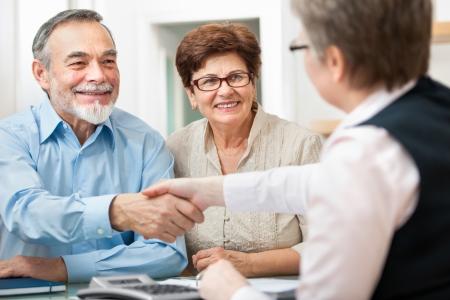senior paar lachend tijdens het schudden hand met financieel adviseur Stockfoto