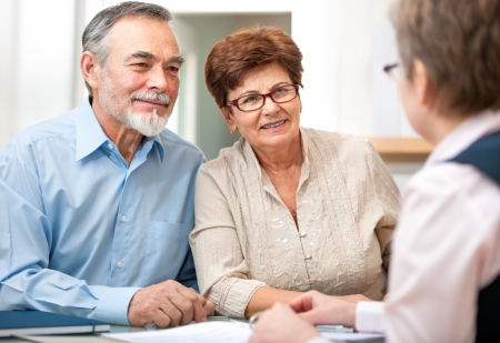 financial agreement: Senior couple discussing financial plan with consultant