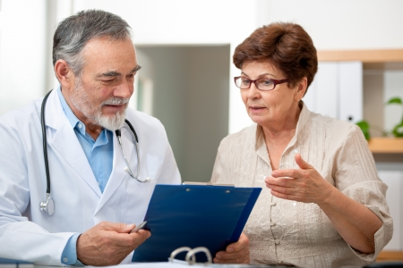 doctor burnout: doctor talking to his female patient at office Stock Photo