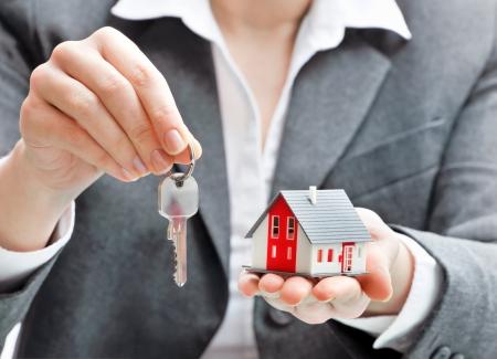реальный: Агент по недвижимости с моделью дома и ключи Фото со стока