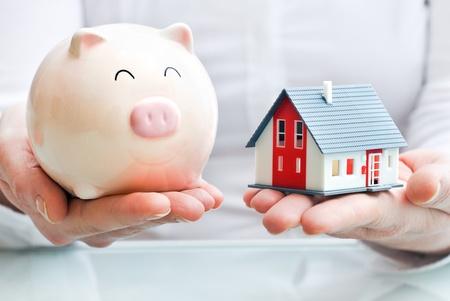 Manos sosteniendo una hucha y un modelo de la casa de Vivienda plan de hipoteca residencial industria y la estrategia de ahorro fiscal Foto de archivo