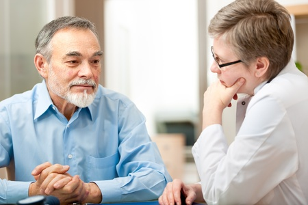 doctor burnout: Male patient tells the doctor about his health complaints Stock Photo