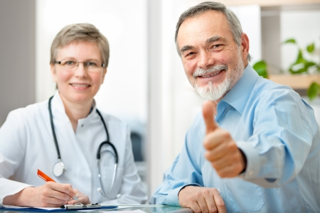 mature doctor: Happy senior patient and doctor at the doctor