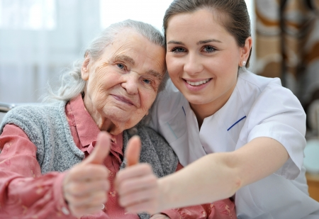 Senior woman and female nurse are showing thumbs up
