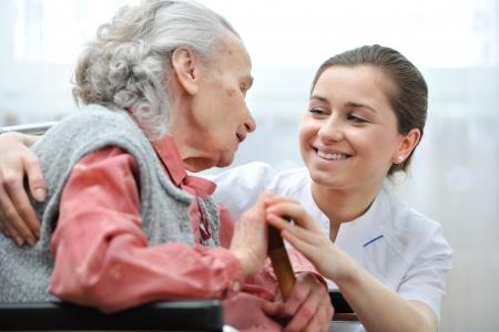 discapacidad: Mujer mayor con su cuidador en el hogar