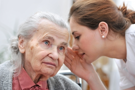Female nurse is speaking in senior woman ear photo