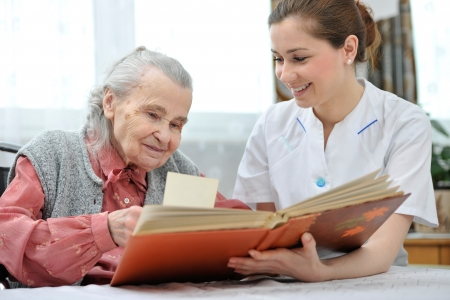 hospice: Senior woman and nurse looking together at album with old photographs Stock Photo