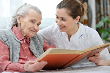enfermeria: Mujer mayor y enfermera mirando juntos en álbum con fotografías antiguas