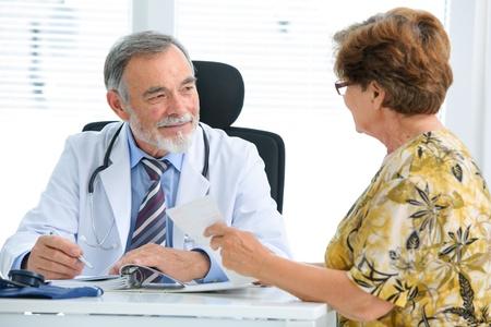 Dottore parlando con il suo paziente femminile senior presso l'ufficio Archivio Fotografico - 20785510