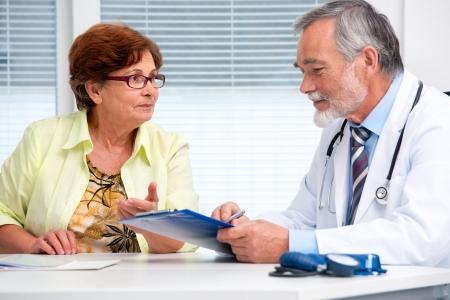 medico con paciente: Doctor que habla con su paciente mujer senior en la oficina