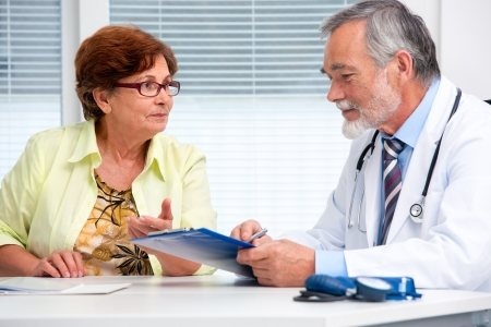 patient and doctor: Doctor talking to his female senior patient at the office