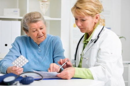 doctor prescribes medication to the senior patient photo