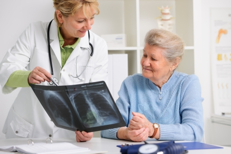 mature doctor: doctor and patient discussing scan results at the office Stock Photo