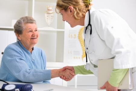 consulta médica: médico estrechar la mano con la paciente senior feliz