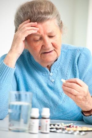 薬を服用、年上の女性のクローズ アップの肖像画