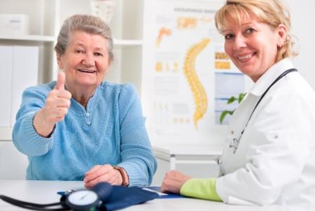 醫療保健: 快樂的高級病人和醫生在醫生 版權商用圖片