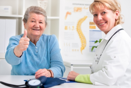 patient and doctor: Happy senior patient and doctor at the doctor
