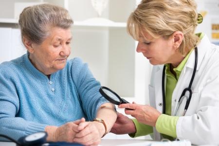 zvětšovací: Žena lékař zkoumá krtka u pacienta Reklamní fotografie
