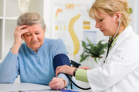 Doctor measuring blood pressure of senior patient Stock Photo