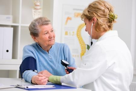 pressure gauge: Doctor measuring blood pressure of senior patient Stock Photo