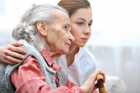 Senior woman with her caregiver at home photo