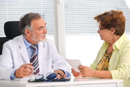 prescribe: Doctor talking to his female senior patient at the office