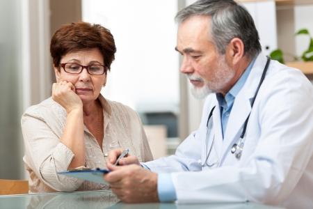 paciente: Doctor que habla con su paciente mayor femenino en la oficina