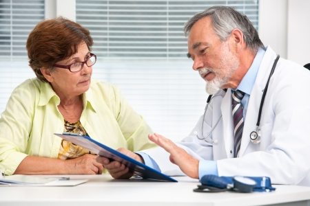 doctor visit: Doctor talking to his female senior patient at the office