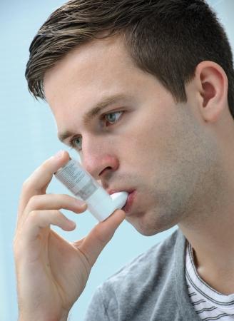 asma: Hombre joven que usa un inhalador para el asma como la prevención