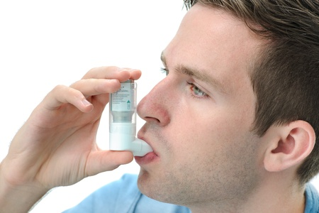 bronchitis: Young man using  an asthma inhaler as prevention