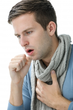 asthma: portrait of an young man coughing with fist