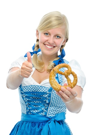 Bavarian girl in oktoberfest dirndl with pretzel shows thumb up photo