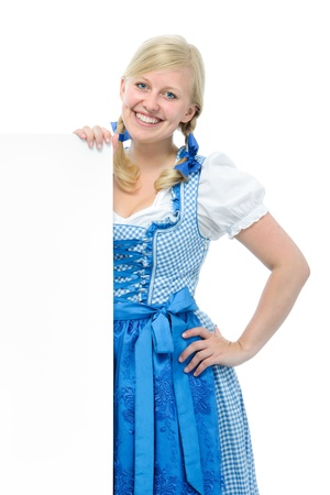 dirndl: young woman in dirndl holds ad space and smile Stock Photo