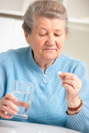 swallowing: close-up portrait of an older woman taking a medicine