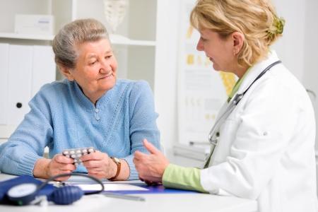 arts schrijft medicatie aan de hogere patiënt Stockfoto