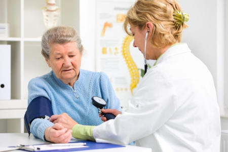 Doctor measuring blood pressure of senior patient photo