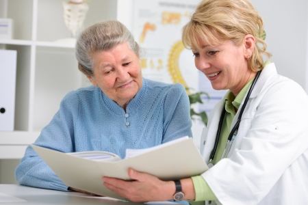 doctor talking to her female patient at office Stock Photo
