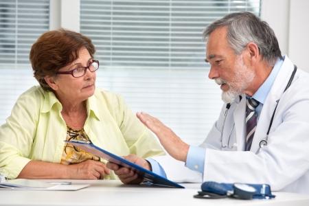 consulta médica: Doctor que habla con su paciente mujer senior en la oficina