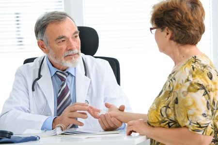 patient and doctor: Physician examines the injured hand of the patient