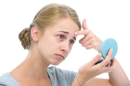 10 代の少女は鏡の中のにきびのための彼女の顔をチェック 写真素材