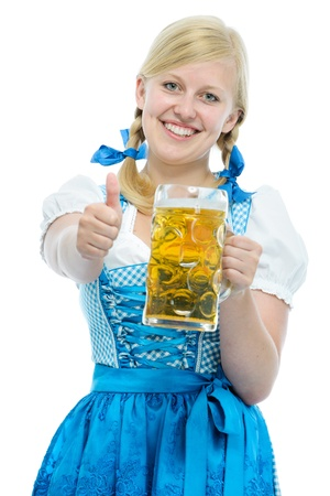 Bavarian girl in Oktoberfest dirndl holds Oktoberfest beer stein and  shows thumb up
