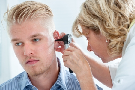 physical exam: Medico ORL cercando nell'orecchio del paziente con uno strumento