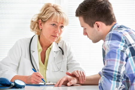 doctor talking to her male patient at office