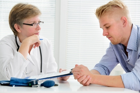 abusive man: doctor talking to her male patient at office